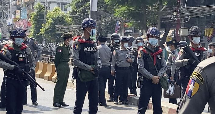 In this image made from video, Myanmar police block the road to prevent protesters from marching forward Saturday, Feb. 6, 2021 in Yangon, Myanmar