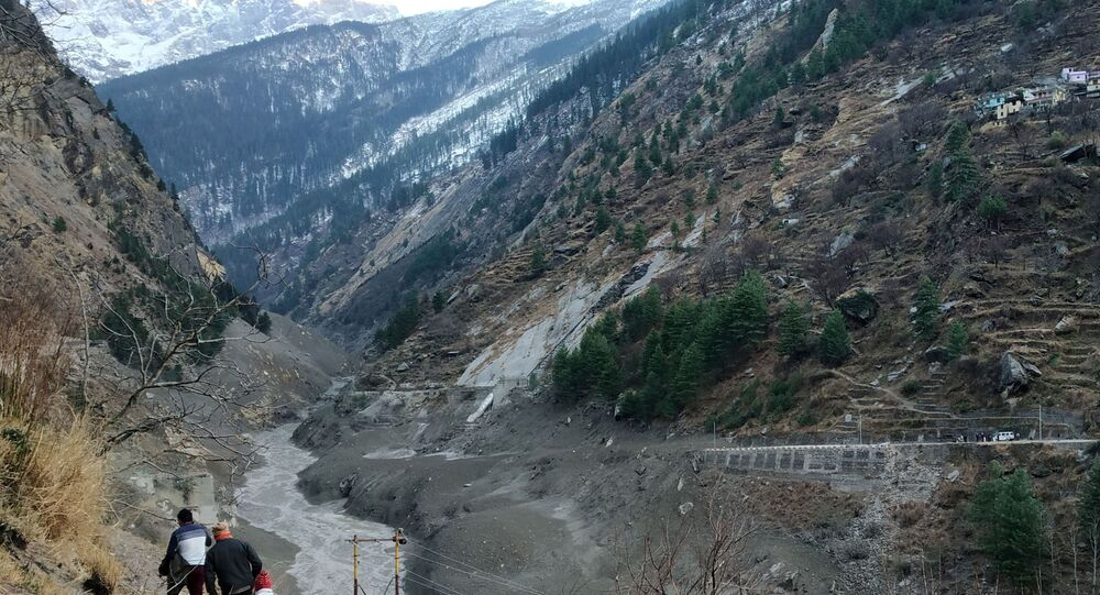 People walk past a destroyed dam after a Himalayan glacier broke and crashed into the dam at Raini Chak Lata village in Chamoli district, northern state of Uttarakhand, India, February 7, 2021.