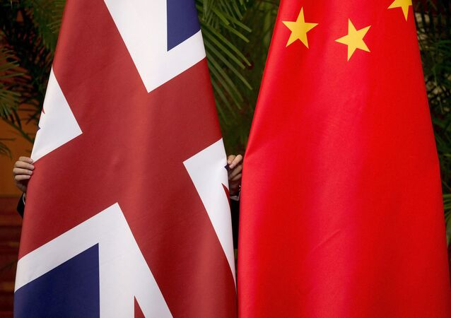 A worker adjusts British and China (R) national flags on display for a signing ceremony at the seventh UK-China Economic and Financial Dialogue Roundtable on Public-Private Partnerships at Diaoyutai State Guesthouse in Beijing, China September 21, 2015
