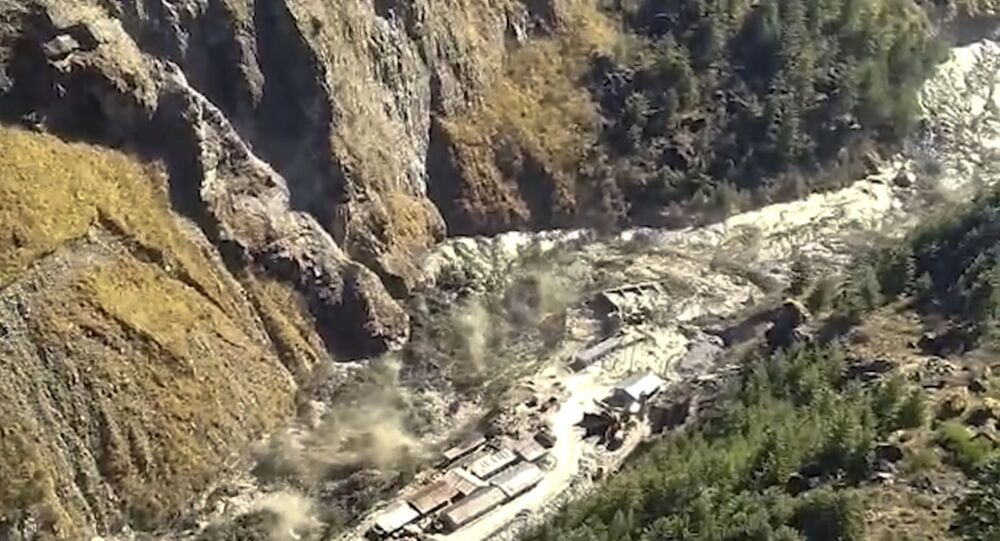 This frame grab from video provided by KK Productions shows a massive flood of water, mud and debris flowing at Chamoli District after a portion of Nanda Devi glacier broke off in Tapovan area of the northern state of Uttarakhand, India, Sunday, Feb.7, 2021. (KK Productions via AP)