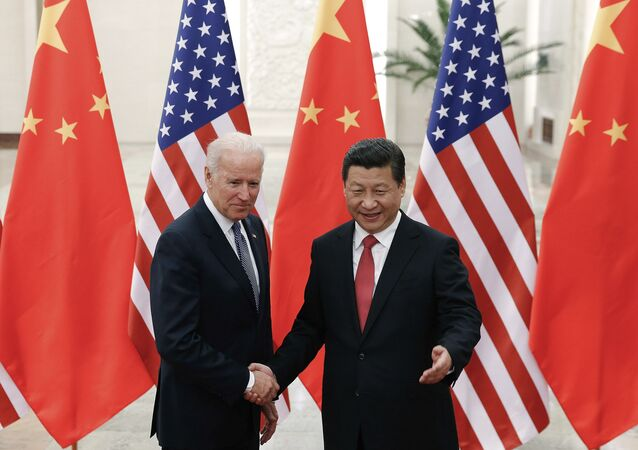 FILE - In this Dec. 4, 2013, file photo, Chinese President Xi Jinping, right, shakes hands with then U.S. Vice President Joe Biden as they pose for photos at the Great Hall of the People in Beijing.