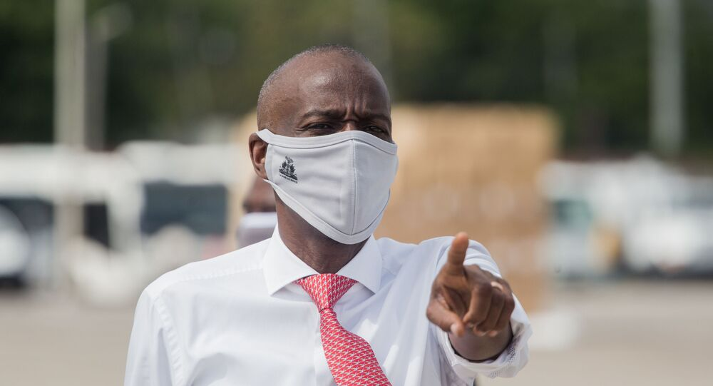 In this file photo taken on May 7, 2020 Haitian President Jovenel Moise instructs staff members on the tarmac of  Toussaint Louverture International Airport in Port-au-Prince, as coronavirus aid from China arrives in a cargo plane.