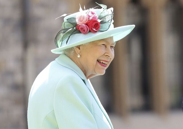 Britain's Queen Elizabeth smiles after awarding Captain Sir Thomas Moore his knighthood during a ceremony at Windsor Castle in Windsor, England, Friday, July 17, 2020.