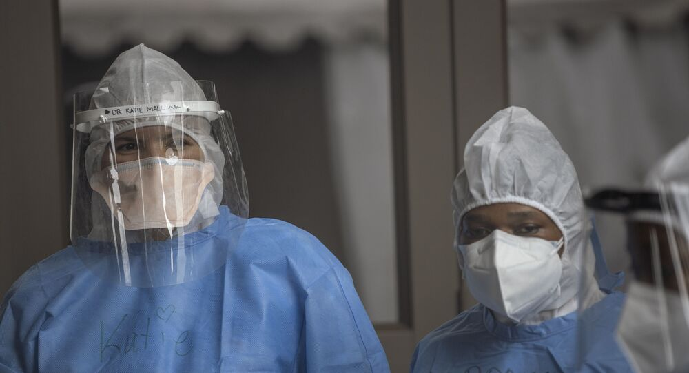 Healthcare workers wearing personal protective equipment (PPE) stand outside one of the temporary wards dedicated to the treatment of possible COVID-19 coronavirus patients at the Nasrec Field Hospital in Soweto, on January 25, 2021.