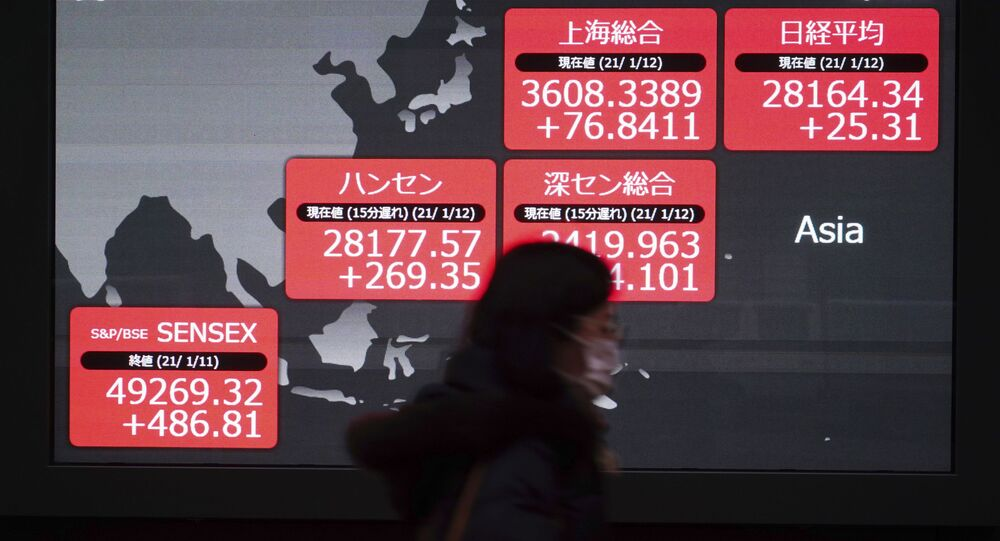 A woman wearing a face mask to help curb the spread of the coronavirus walks past an electronic stock board showing Japan's Nikkei 225 and other Asian indexes at a securities firm in Tokyo Tuesday, Jan. 12, 2021.