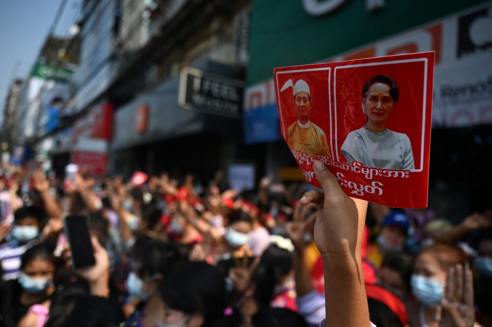 A protester holds up a sign with the images of detained Myanmar civilian leader Aung San Suu Kyi (R) and president Win Myint during a demonstration against the military coup in Yangon on 6 February 2021.