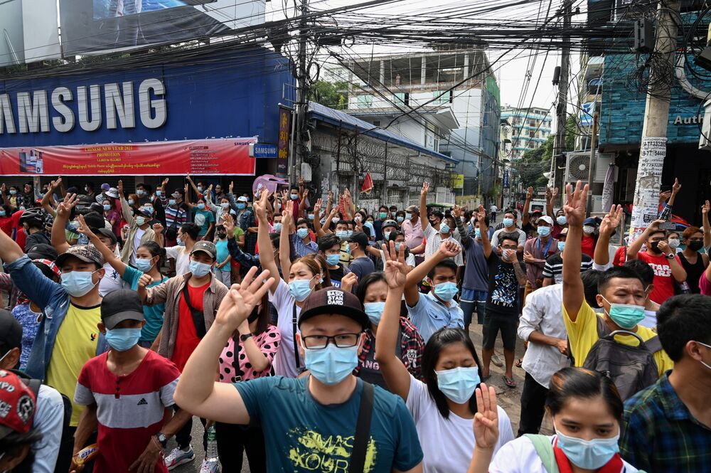 Protesters hold up the three finger salute during a demonstration against the military coup in Yangon on 6 February 2021.