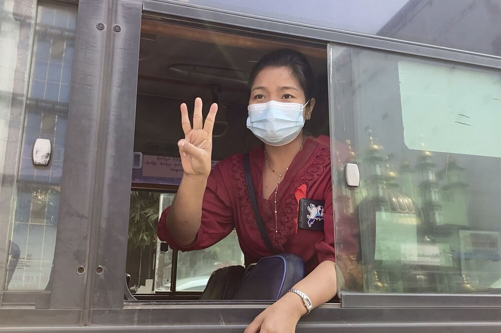In this image made from video, a woman flashes the three-fingered salute from a vehicle as a crowd of protesters march past Saturday 6 February 2021, in Yangon, Myanmar.  The military authorities in charge of Myanmar broadened a ban on social media following this week's coup, shutting access to Twitter and Instagram, while street protests continued to expand Saturday as people gathered again to show their opposition to the army takeover.