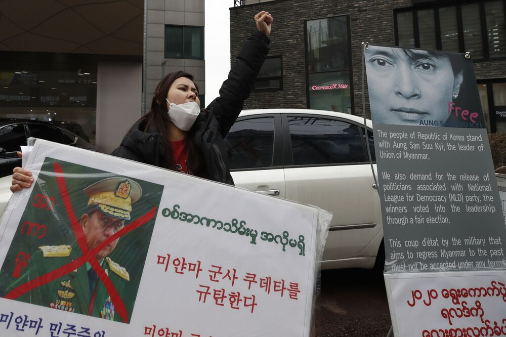 A Myanmar woman living in South Korea shouts slogans as she holds a banner with a defaced picture of Myanmar military Commander-in-Chief Senior Gen. Min Aung Hlaing during a rally against the military coup near the office of the military attache of the Myanmar embassy, in Seoul, South Korea, Saturday, 6 February 2021.
