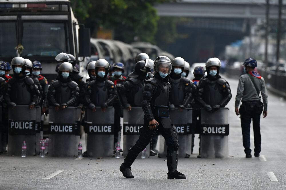 Riot police block a street as protesters gather for a demonstration against the military coup in Yangon on 6 February 2021.