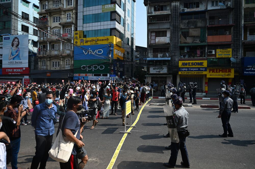 Protesters face off against riot police blocking a street during a demonstration against the military coup in Yangon on 6 February 2021.