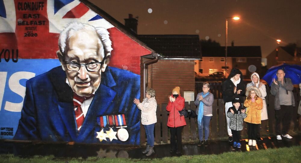 Local residents join a national clap beside a mural of Captain Sir Tom Moore in East Belfast, Northern Ireland, Wednesday, Feb. 3, 2021. Captain Moore passed away Tuesday after being treated with Covid-19 and was known for his achievements raising millions of pounds for the NHS charity during the Covid-19 pandemic.
