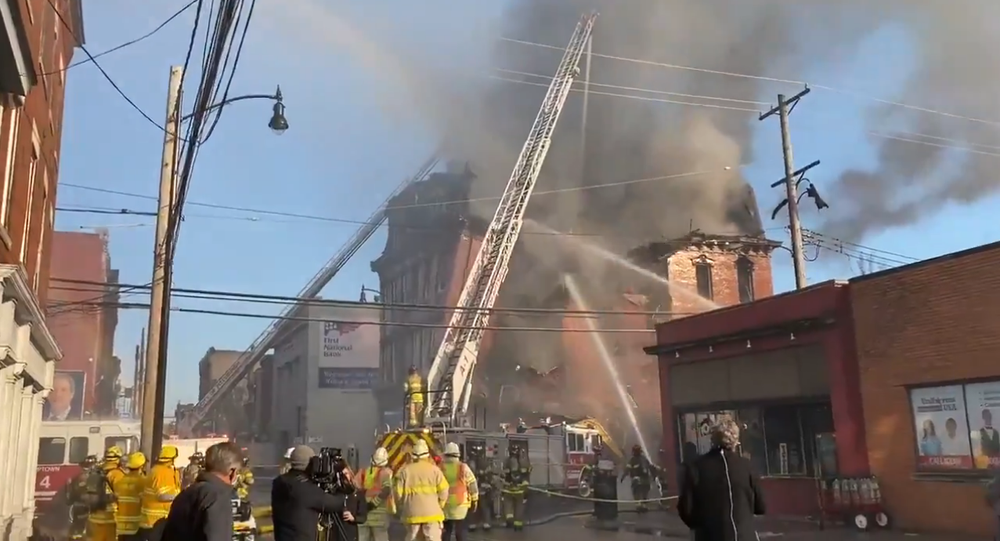 Screenshot from the video showing a commercial building collapsing due to massive fire in Pittsburgh