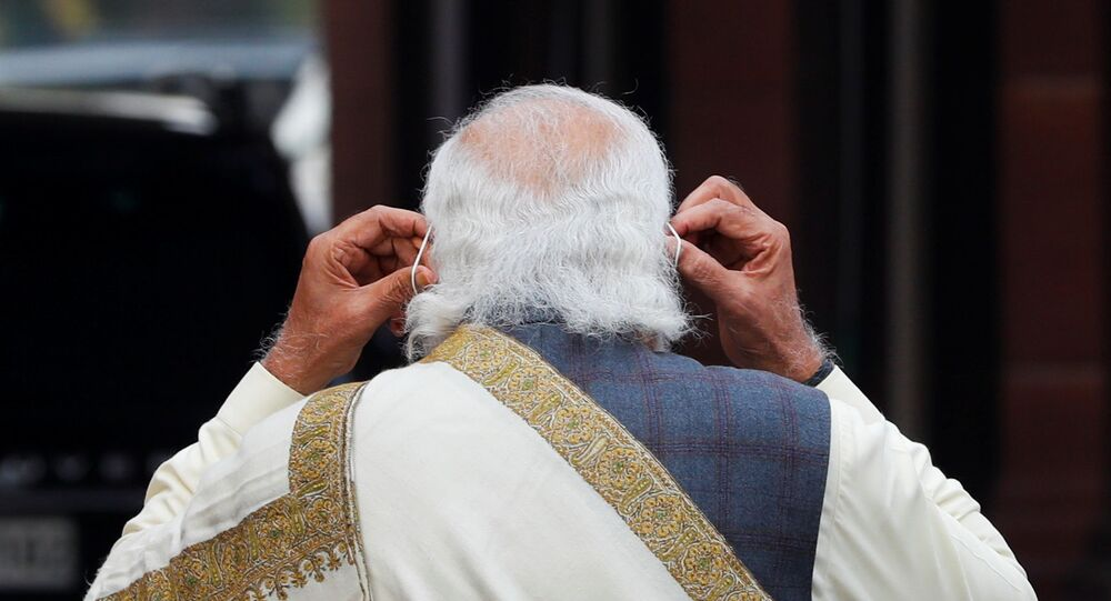 India's Prime Minister Narendra Modi adjusts his protective mask after speaking with the media