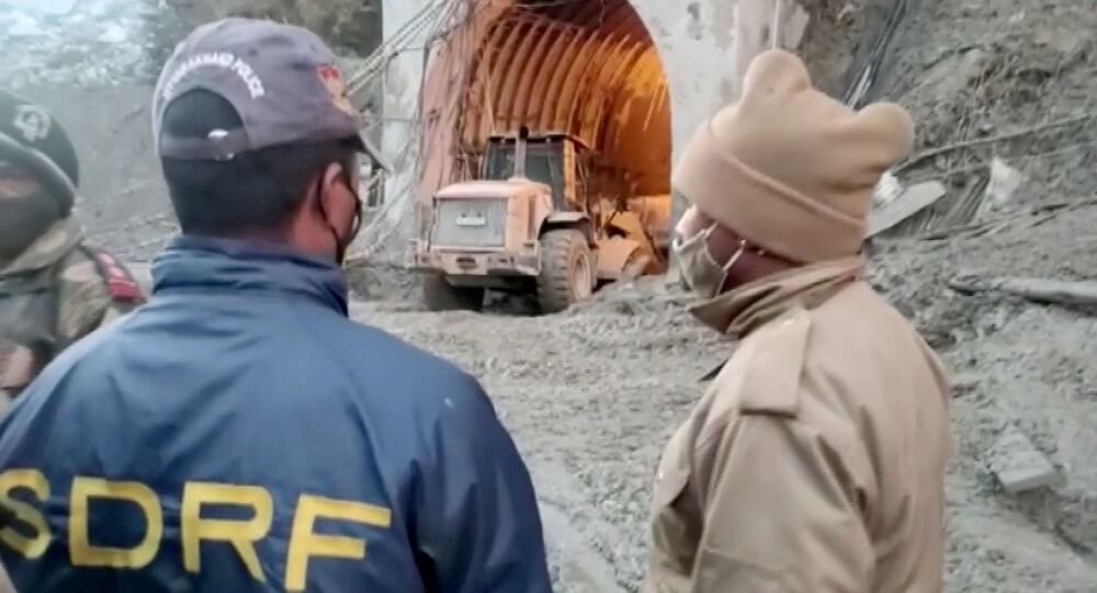 Excavator exits a tunnel in Chamoli, Uttarakhand, India during a rescue operation after a glacier burst, in this still frame taken from video dated February 8, 202