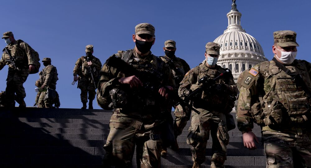 Members of the National Guard walk past the dome of the Capitol Building on Capitol Hill in Washington, Thursday, Jan. 14, 2021
