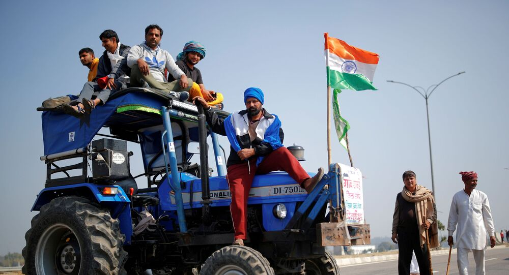 Farmers stand atop a tractor as they take part in a three-hour chakka jam, or road blockade, as part of protests against farm laws on a highway on the outskirts of New Delhi
