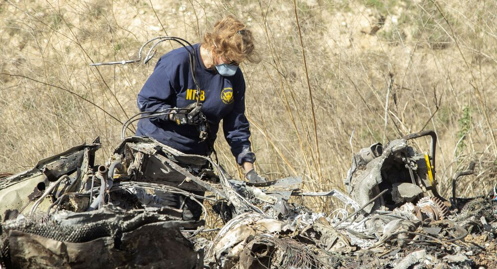 FILE - In this Jan. 27, 2020, file photo, released by the National Transportation Safety Board, NTSB investigator Carol Hogan examines wreckage as part of the NTSB's investigation of a helicopter crash near Calabasas, Calif., that killed former NBA basketball player Kobe Bryant, his 13-year-old daughter, Gianna, and seven others. Federal safety investigators bypassed aviation regulators on Tuesday, June 2, 2020, and urged leading helicopter manufacturers to install so-called black boxes that would help determine the cause of crashes such as the one that killed former NBA star Kobe Bryant.