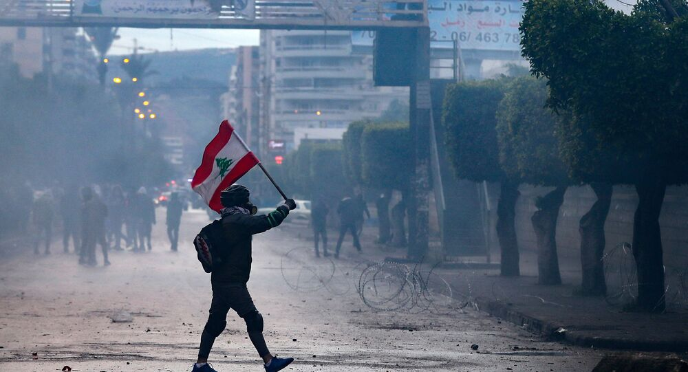 A Lebanese anti-government protester waves a national flag during clashes with security forces in front of the Serail (headquarters of the Governorate), in the northern port city of Tripoli, following a demonstration to protest against the economic situation, on January 28, 2021.