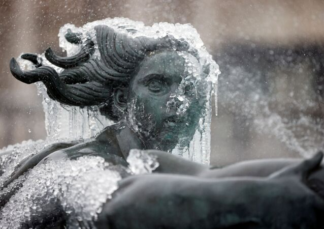 A statue inside the fountain on Trafalgar Square in London is seen covered with icicles and frozen water as Storm Darcy affects large parts of the country on 8 February 2021.
