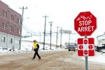 A man wearing a mask to help slow the spread of coronavirus disease (COVID-19) passes a stop sign written in English, French and Inuktitut as the territory of Nunavut enters a two week mandatory restriction period in Iqaluit, Nunavut, Canada 18 November 2020.