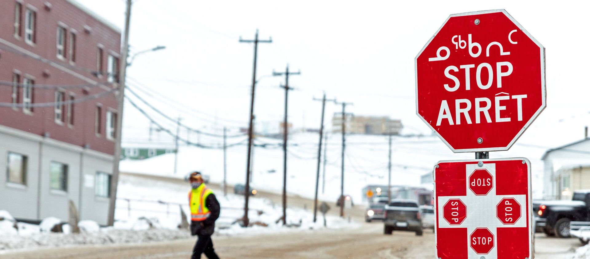 A man wearing a mask to help slow the spread of coronavirus disease (COVID-19) passes a stop sign written in English, French and Inuktitut as the territory of Nunavut enters a two week mandatory restriction period in Iqaluit, Nunavut, Canada 18 November 2020. - Sputnik International, 1920, 02.03.2021