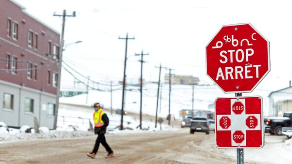 A man wearing a mask to help slow the spread of coronavirus disease (COVID-19) passes a stop sign written in English, French and Inuktitut as the territory of Nunavut enters a two week mandatory restriction period in Iqaluit, Nunavut, Canada 18 November 2020. - Sputnik International