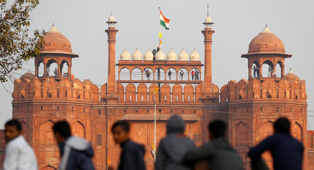 A farmer holds a flag on top of the historic Red Fort, during a protest against farm laws introduced by the government, in Delhi, India