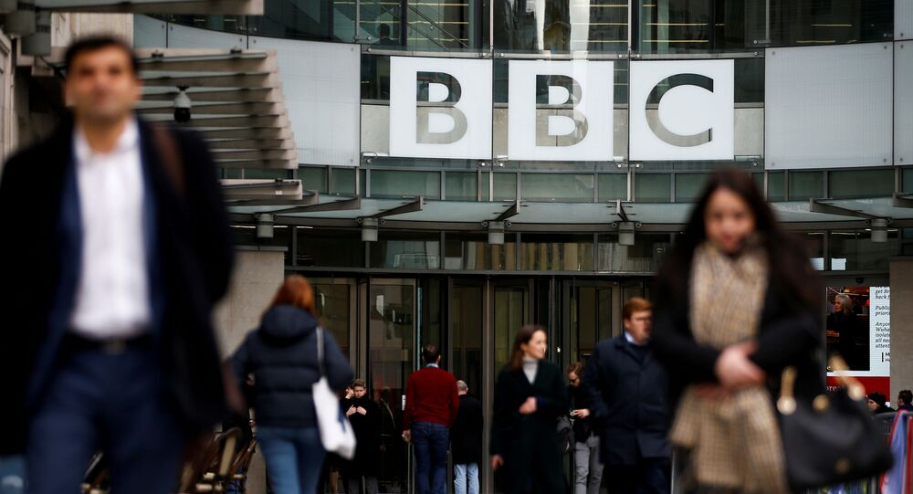 FILE PHOTO: Pedestrians walk past a BBC logo at Broadcasting House in London, Britain January 29, 2020. REUTERS/Henry Nicholls/File Photo