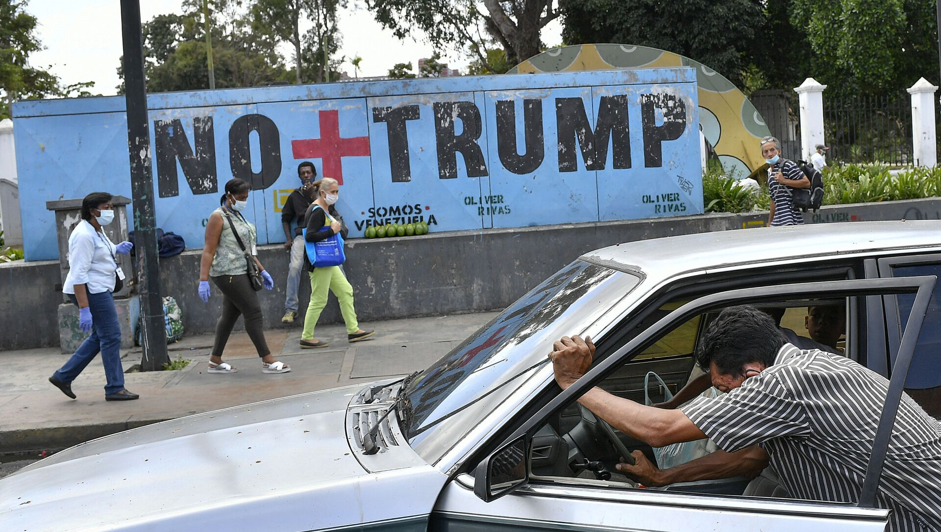 A man pushes his car that ran out of gas as people wearing protective face masks as a precaution against the spread of the new coronavirus, walk past a mural with a message that reads in Spanish:  No more Trump in Caracas, Venezuela, Sunday, Nov. 8, 2020. Venezuelan President Nicolas Maduro has sent a congratulatory message to U.S. President-elect Joe Biden who won the U.S. presidential election, defeating incumbent Donald Trump. - Sputnik International, 1920, 17.03.2021