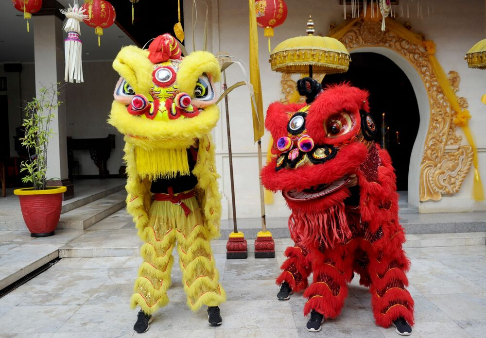 Two lion dancers prepare to pray at a Chinese temple on the first day of the Lunar New Year in Kuta, on Indonesia's resort of Bali on 12 February 2021.
