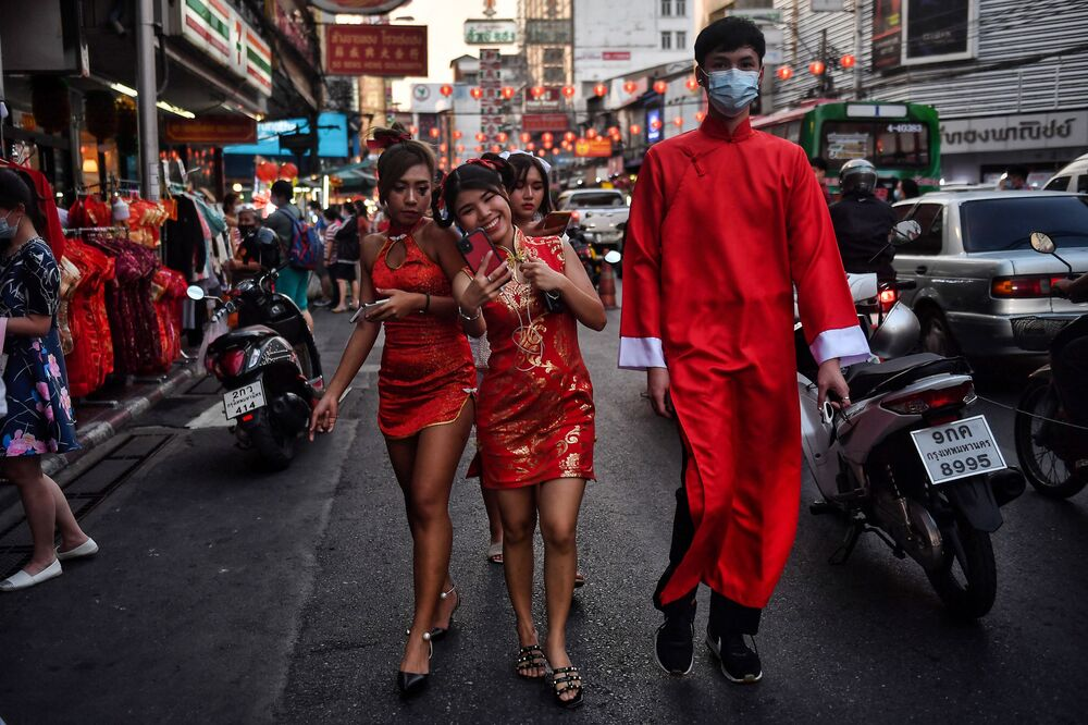 People wear traditional Chinese outfits as they walk in Chinatown in Bangkok on 11 February 2021 ahead of the start of the Lunar New Year, which ushers in the Year of the Ox on 12 February.