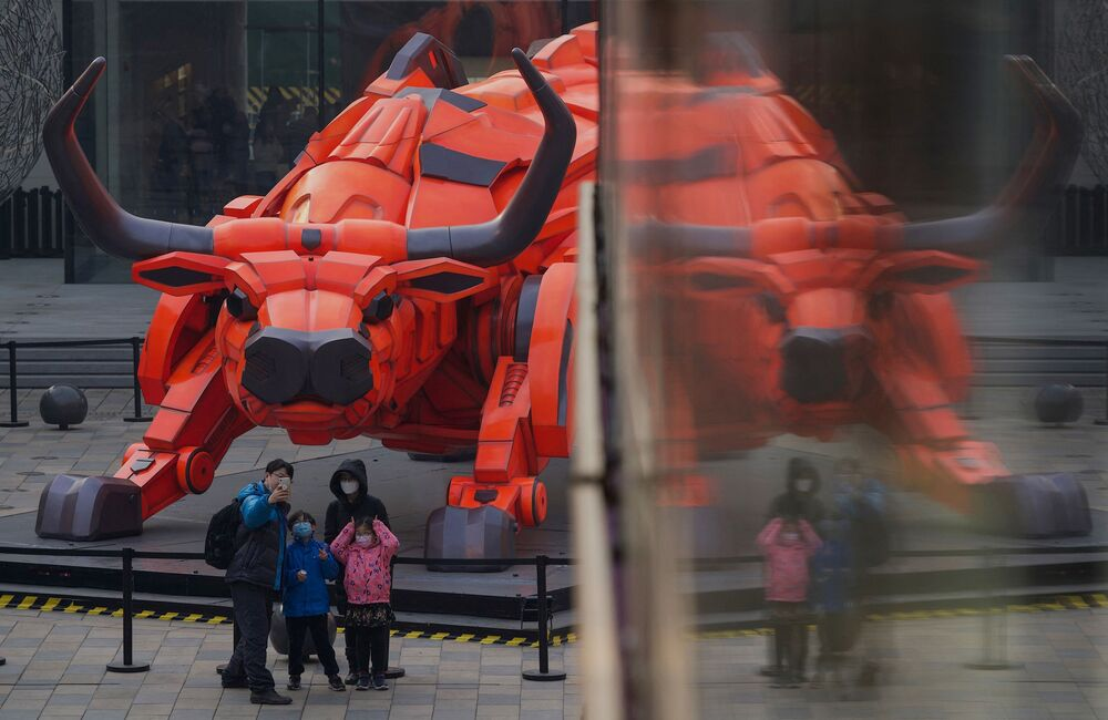 A family take a picture in front of a bull sculpture at a mall in Beijing on 11 February 2021, ahead the biggest holiday of the year, the Lunar New Year, which ushers in the Year of the Ox on February 12.