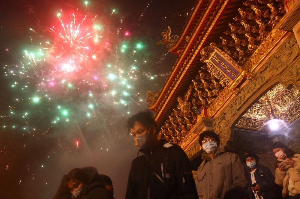 People watch Lunar New Year fireworks while wearing protective masks to prevent the spread of the coronavirus disease (COVID-19) as they wait to enter a temple in Taipei, Taiwan, 12 February 2021.