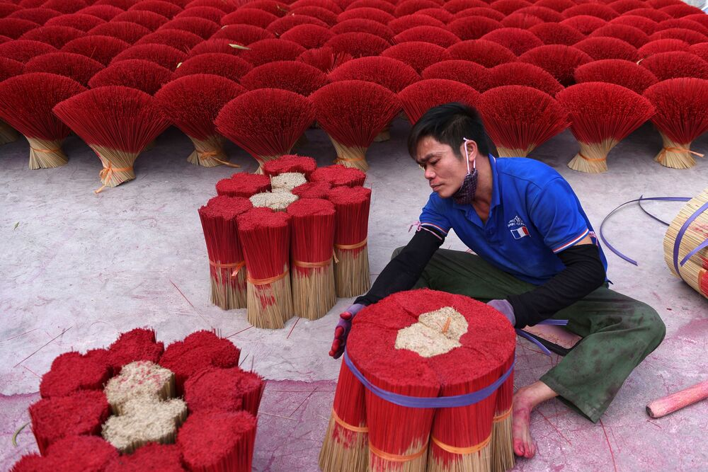 A worker packs dried incense sticks in a courtyard ahead of Lunar New Year celebrations in Quang Phu Cau village outside Hanoi, Vietnam, 3 February 2021.