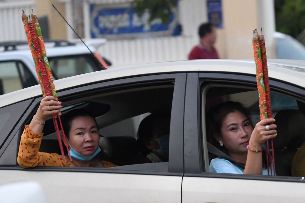 Women hold incense sticks while on a car after visiting a temple to mark the start of the Lunar New Year in Ta Khmao, Kandal province in Cambodia on 12 February 2021.