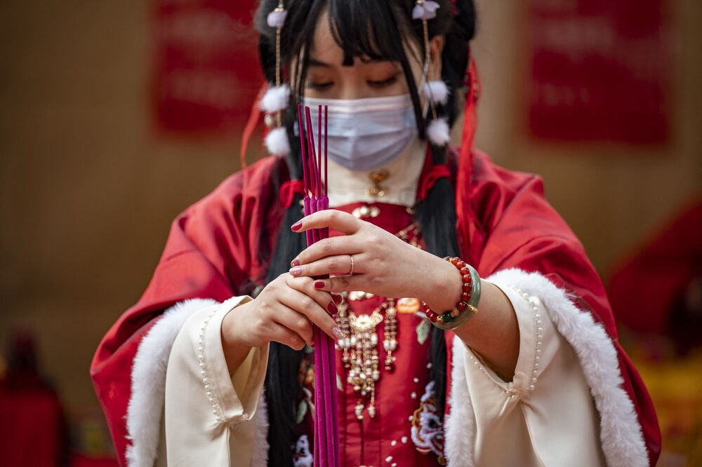 A woman wearing a traditional outfit burns incense and prays at Ma Zhu Miao temple on the first day of the Lunar New Year of the Ox in Yokohama's Chinatown area in Japan on 12 February 2021.