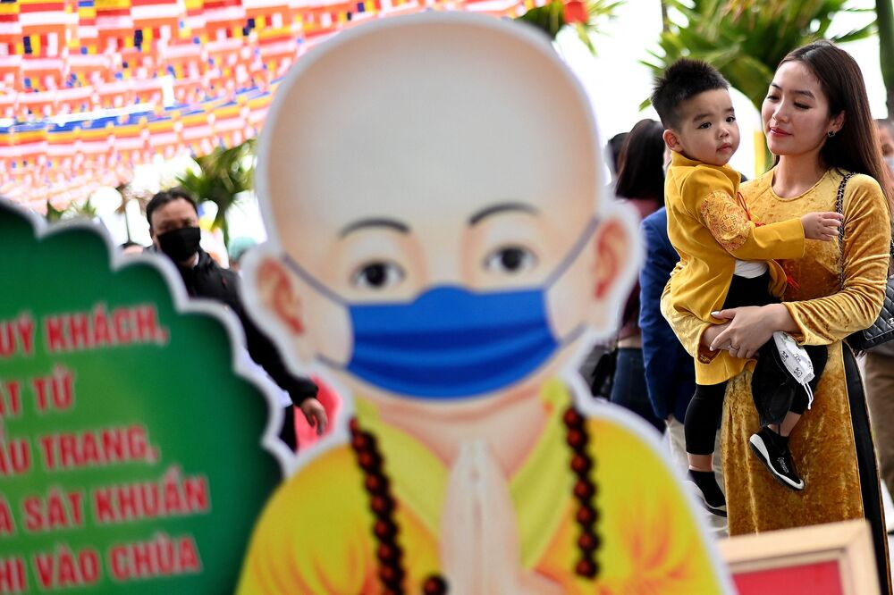 A Vietnamese woman carries her child next to a cut-out illustration of a monk advising visitors to wear face masksat the Tran Quoc Pagoda, one of the oldest pagodas in Hanoi on 12 February 2021 on the first day of Lunar New Year or Tet celebrations.