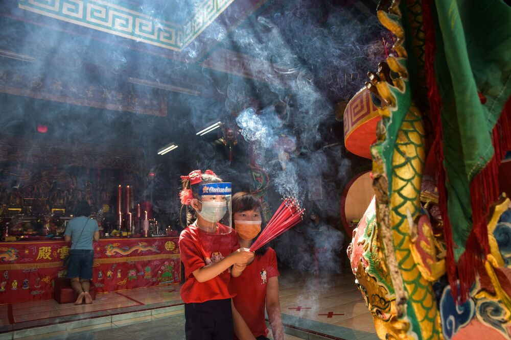 A girl wearing a protective mask and face shield, holds incense sticks while praying with her mother at the Surya Dharma temple during the Chinese Lunar New Year celebrations in Pekanbaru, Riau province, Indonesia, 12 February 2021 in this photo taken by Antara Foto.