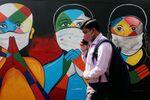 A man walks past a graffiti of people wearing protective masks amidst the spread of the coronavirus disease (COVID-19) on a street in Navi Mumbai, India