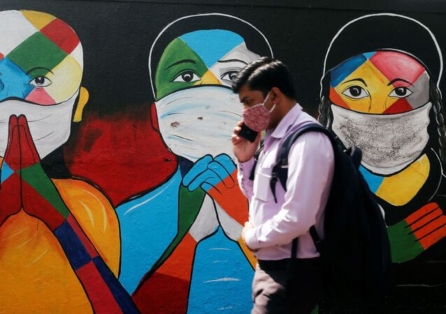A man walks past a graffiti of people wearing protective masks amidst the spread of the coronavirus disease (COVID-19) on a street in Navi Mumbai (New Bombay), India.
