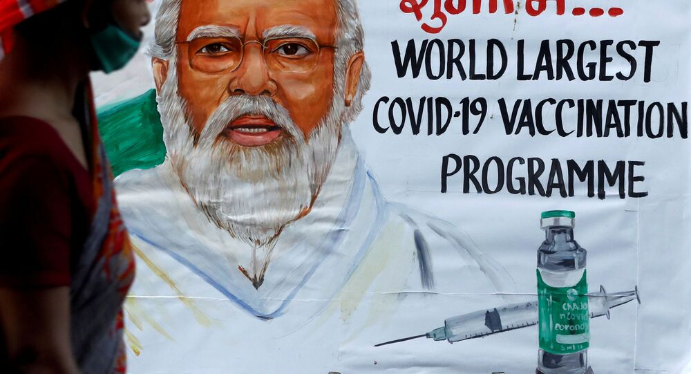 A woman walks past a painting of Indian Prime Minister Narendra Modi a day before the inauguration of the COVID-19 vaccination drive on a street in Mumbai, India