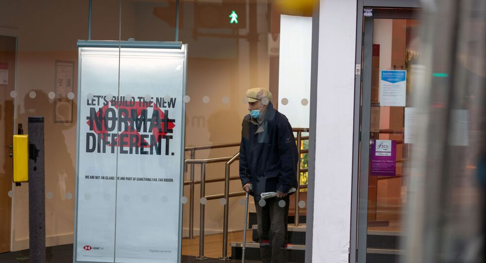 man wearing a face mask looks from a window of an HSBC bank as Britain began its third COVID-19 lockdown in Fulham, London, Britain, January 5, 2021.