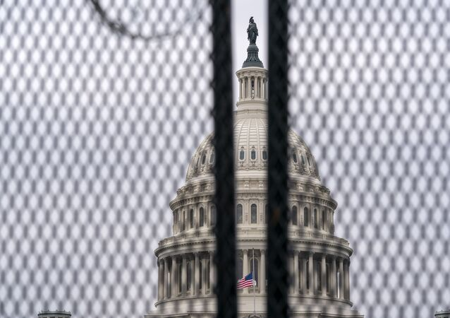 The U.S. Capitol is seen through a fence with barbed wire during the second impeachment trial of former President Donald Trump in Washington, Friday, Feb. 12, 2021.
