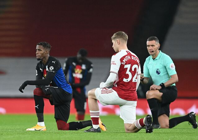 Crystal Palace's Ivorian striker Wilfried Zaha (L), Arsenal's English midfielder Emile Smith Rowe (2nd R) and English referee Andre Marriner (R) 'take the knee' in support of the No Room For Racism campaign.