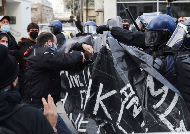 Protesters and activists clash with riot police during a rally against corruption and COVID-19 restriction measures, in Nicosia, Cyprus February 13, 2021