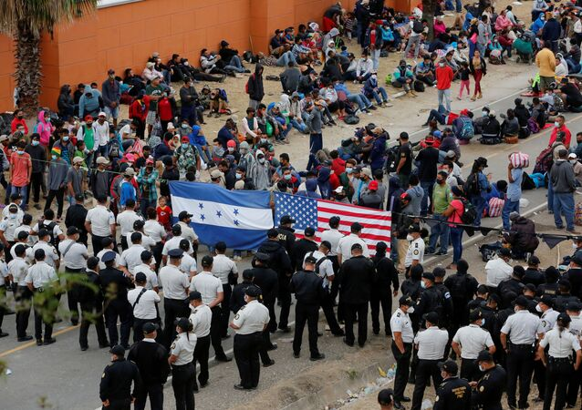 Hondurans taking part in a new caravan of migrants, set to head to the United States, gather in front of police officers blocking the road in Vado Hondo, Guatemala January 18, 2021.