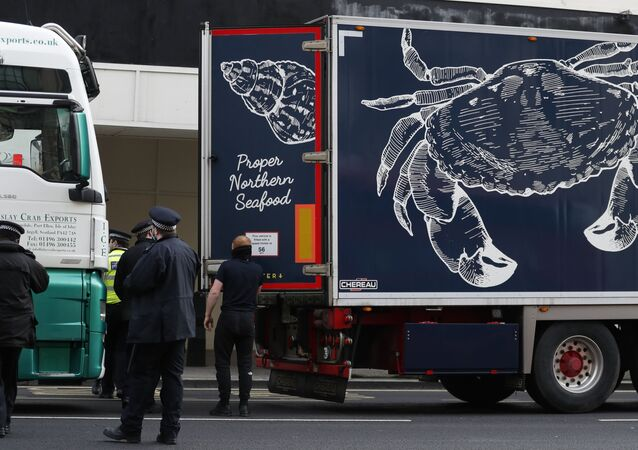 Police speak to shellfish export truck drivers as they are stopped for an unnecessary journey in London, Monday, Jan. 18, 2021, during a demonstration by British Shellfish exporters to protest Brexit-related red tape they claim is suffocating their business.