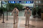 Health workers in suits walk in the international arrivals area, where arriving travelers are to be taken into quarantine, at the international airport in Wuhan on January 14, 2021, ahead of the expected arrival of a World Health Organization (WHO) team investigating the origins of the Covid-19 pandemic. (Photo by NICOLAS ASFOURI / AFP)