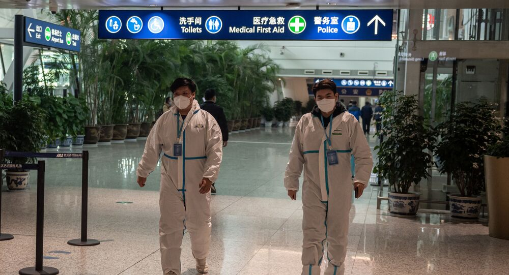 Health workers in suits walk in the international arrivals area, where arriving travellers are to be taken into quarantine, at the international airport in Wuhan on 14 January 2021, ahead of the expected arrival of a World Health Organisation (WHO) team investigating the origins of the Covid-19 pandemic. (Photo by NICOLAS ASFOURI / AFP)